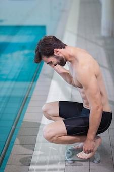 Homem bonito em uma escala de ponderação na piscina