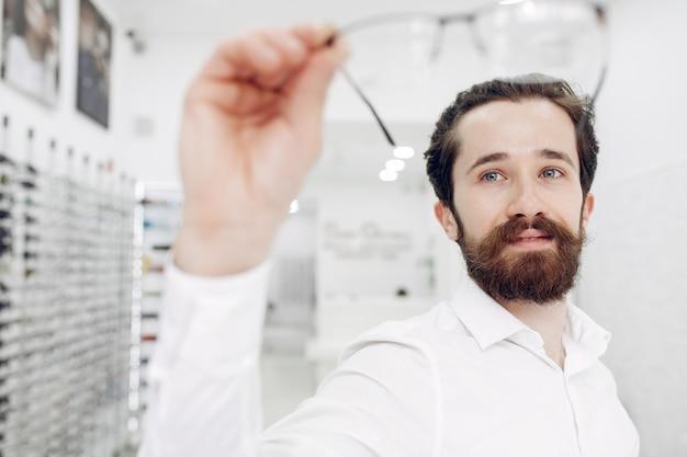 Homem bonito em uma loja de óptica