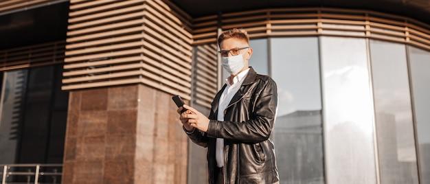 Homem bonito em uma máscara protetora no rosto com óculos com um smartphone na rua de uma cidade grande. empresário falando ao telefone em meio urbano