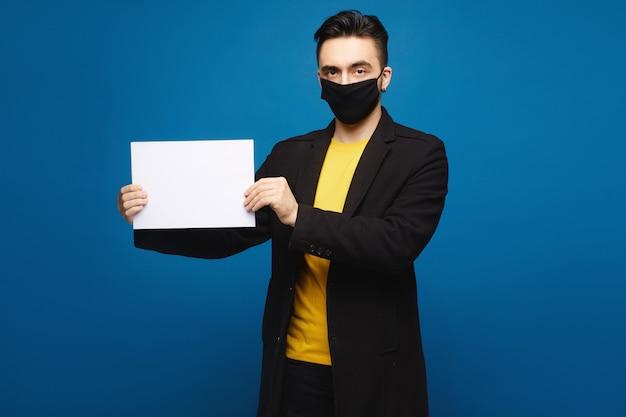 Homem bonito em uma máscara protetora preta segurando uma folha de papel vazia e olhando para a câmera, isolada no fundo azul. conceito de promoção. conceito de saúde