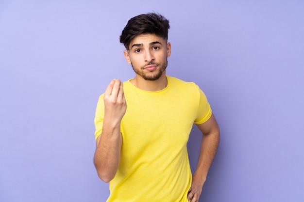 Homem bonito em uma parede isolada fazendo gesto italiano