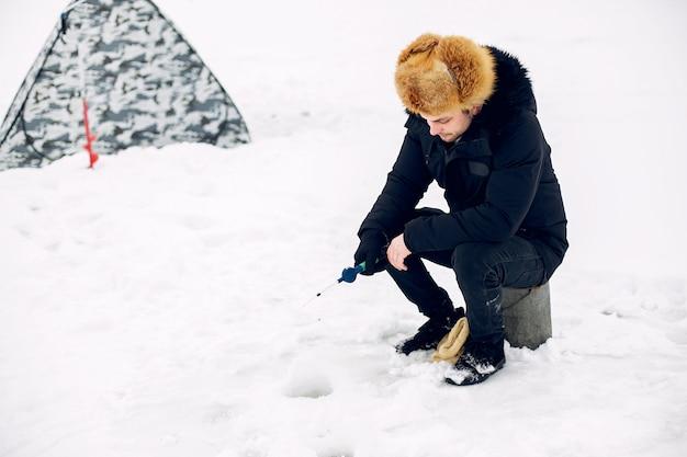Homem bonito em uma pesca de inverno