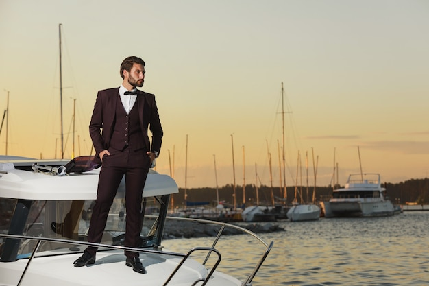 Homem bonito em uma regata. jovem em pé no iate no mar ao pôr do sol