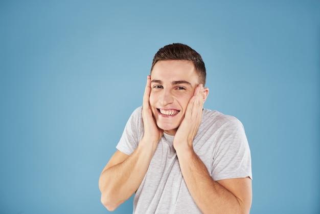 Homem bonito emocional em gesto de t-shirt branca com mãos azuis. foto de alta qualidade