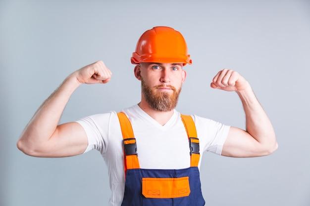 Homem bonito, engenheiro na construção de capacete protetor na parede cinza, olha para a frente e mostra o músculo bíceps
