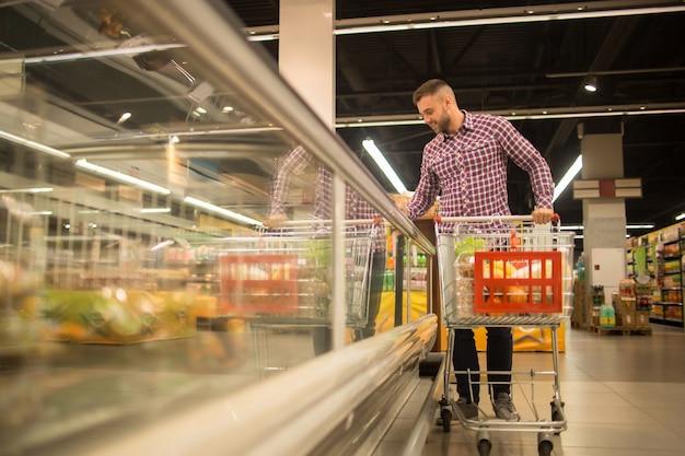 Homem bonito, escolhendo comida no supermercado