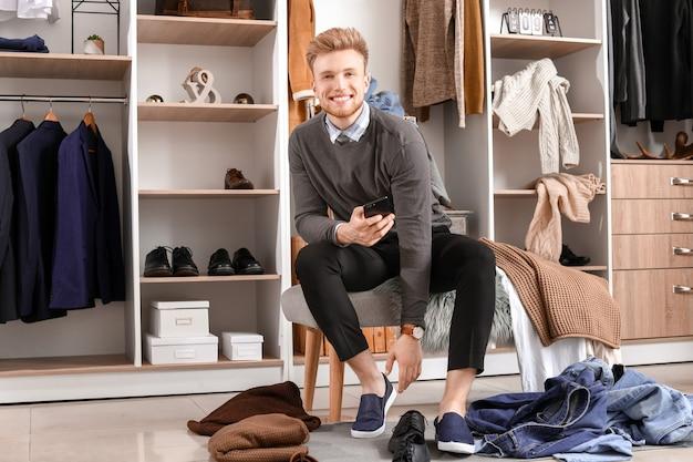 Homem bonito escolhendo roupas em camarim