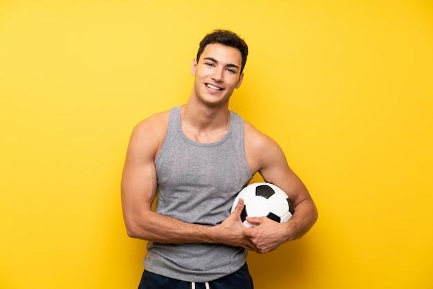 Homem bonito esporte mais isolado com uma bola de futebol