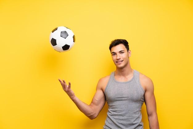 Homem bonito esporte parede isolada com uma bola de futebol