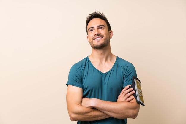Homem bonito esporte sobre fundo isolado, olhando para cima, enquanto sorrindo