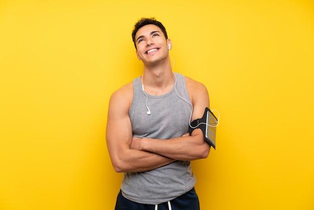 Homem bonito esporte sobre fundo isolado, olhando para cima enquanto sorrindo