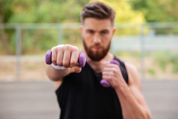 Homem bonito esportes barbudo malhando com pequenos halteres ao ar livre. concentre-se em halteres