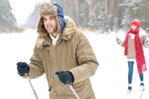 Homem bonito, esquiar na floresta de inverno