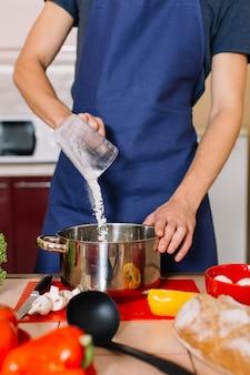 Homem bonito está cozinhando na cozinha e sorrindo