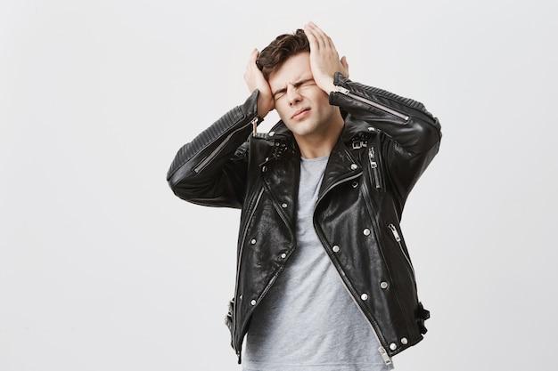 Homem bonito estressante, vestido com jaqueta de couro preta, grita de pânico, fecha os olhos de terror, mantém as mãos na cabeça, descobre más notícias ou desastre sobre o melhor amigo. pessoas, estresse, aborrecimento