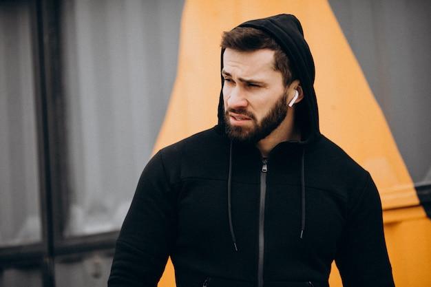 Homem bonito, exercitando-se no parque em roupas esportivas