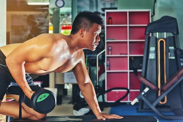 Homem bonito exercitar levantando um haltere para cuidados de saúde em um ginásio público
