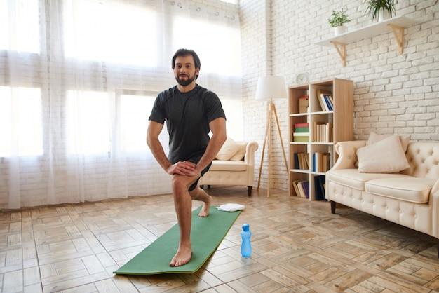 Homem bonito faz exercícios de alongamento em casa.