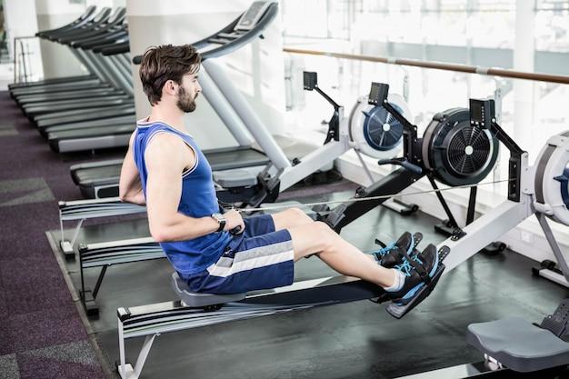 Homem bonito fazendo exercício na máquina de desenho no ginásio