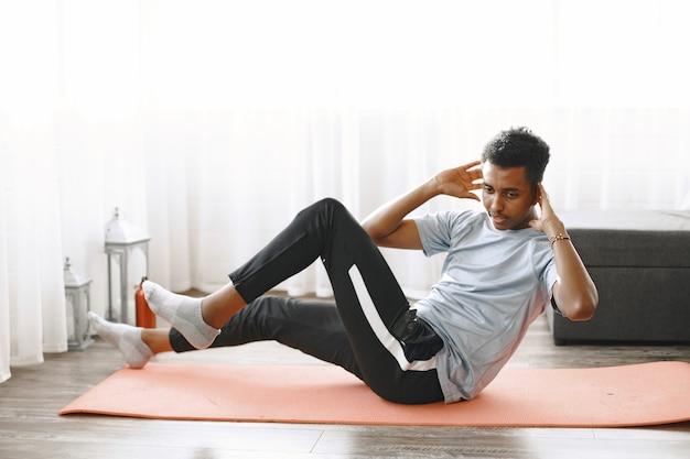 Homem bonito fazendo exercícios abdominais em casa. conceito de vida saudável.