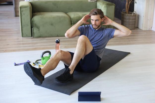 Homem bonito fazendo exercícios abdominais em casa durante a quarentena. conceito de vida saudável.