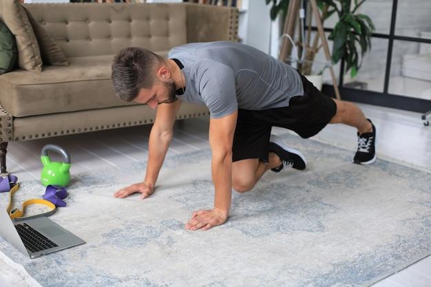 Homem bonito fazendo exercícios abdominais em casa durante a quarentena. conceito de vida saudável