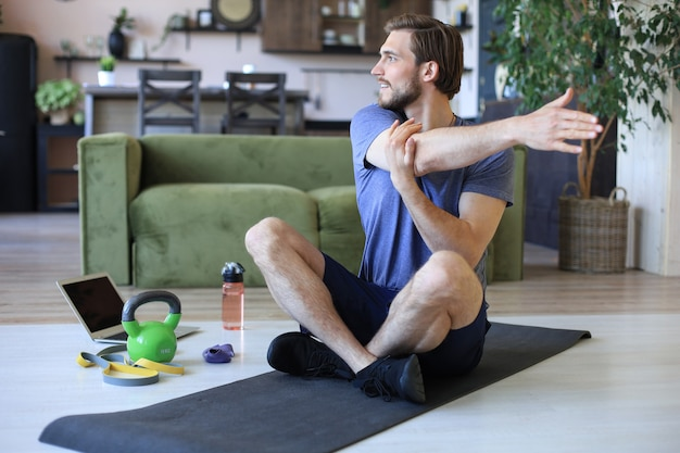Homem bonito, fazendo exercícios de alongamento em casa durante a quarentena. conceito de vida saudável.