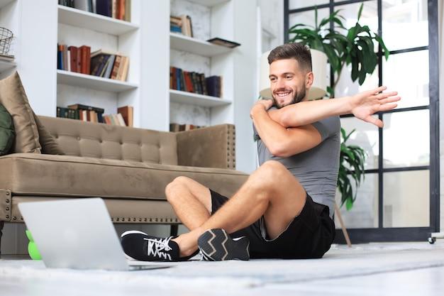 Homem bonito, fazendo exercícios de alongamento em casa durante a quarentena. conceito de vida saudável