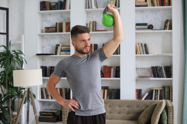 Homem bonito, fazendo exercícios de esporte com kettlebell em casa. conceito de vida saudável.