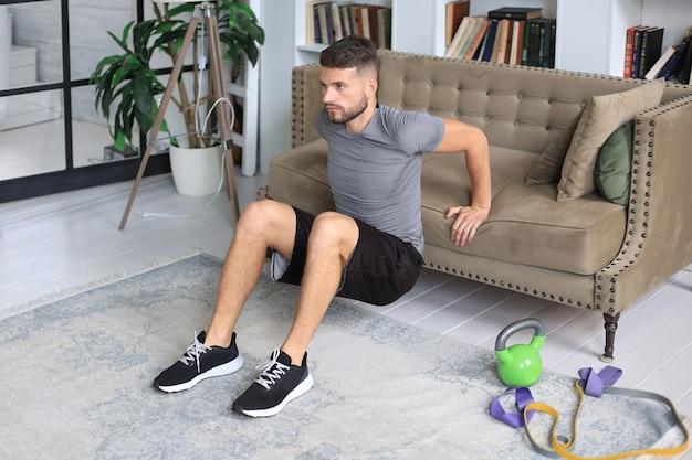 Homem bonito, fazendo exercícios de esporte em casa durante a quarentena. conceito de vida saudável