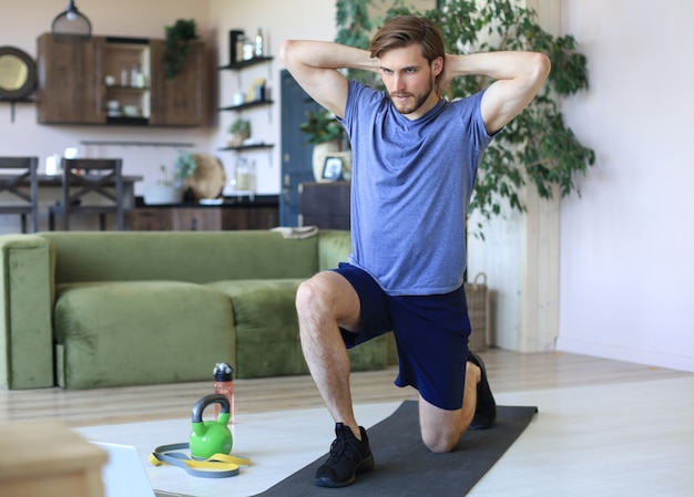 Homem bonito, fazendo exercícios de esporte em casa durante a quarentena. conceito de vida saudável.
