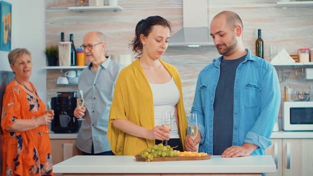 Homem bonito, fazendo proposta para a namorada na frente dos pais, na cozinha, sentado perto da mesa, bebendo uma taça de vinho branco. mulher feliz e surpresa beijando-o enquanto os pais tiram uma foto