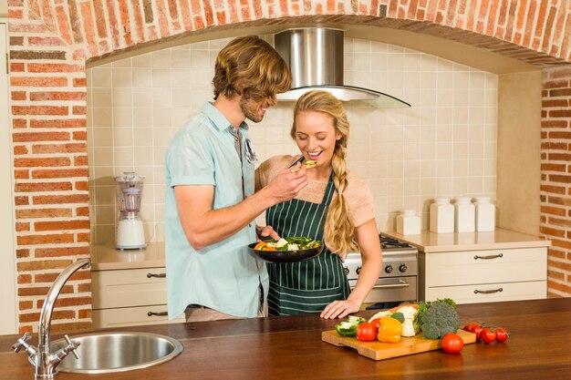 Homem bonito fazendo sua namorada provar a preparação na cozinha