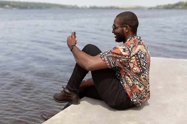 Homem bonito fazendo uma videochamada com smartphone moderno ao ar livre