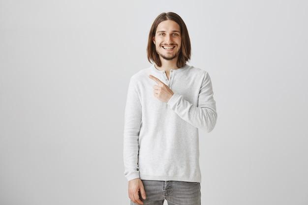 Homem bonito feliz apontando o canto superior esquerdo para o anúncio