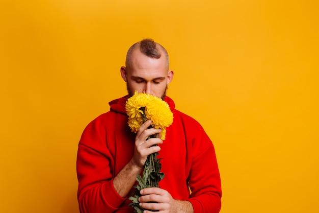 Homem bonito feliz com buquê de flores de ásteres amarelos