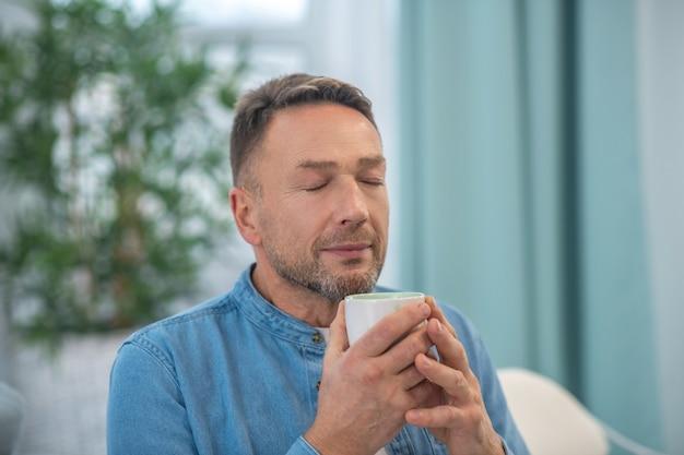 Homem bonito feliz com uma xícara nas mãos, fechando os olhos, de bom humor.