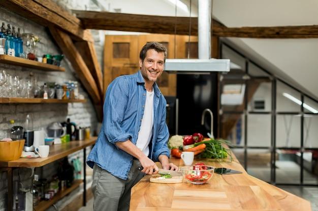 Homem bonito feliz cozinhando na cozinha em casa