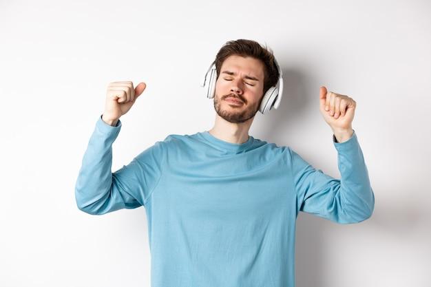 Homem bonito feliz dançando música em fones de ouvido, ouvindo músicas e sorrindo, em pé sobre um fundo branco.