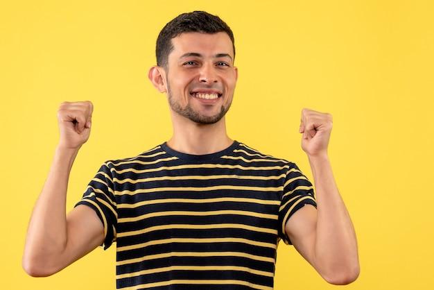 Homem bonito feliz de vista frontal em uma camiseta listrada de preto e branco amarelo isolado de fundo