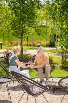Homem bonito feliz e alegre e uma senhora loira caucasiana sentados nas poltronas, curtindo a companhia um do outro