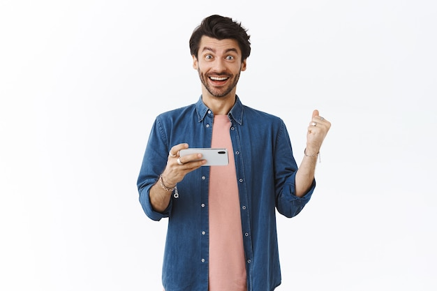 Homem bonito feliz e aliviado, segurando o smartphone horizontalmente e erguendo o punho como se estivesse com sorte, ganhando o prêmio no jogo, parece surpreso, sorrindo alegremente, comemorando a vitória, parede branca