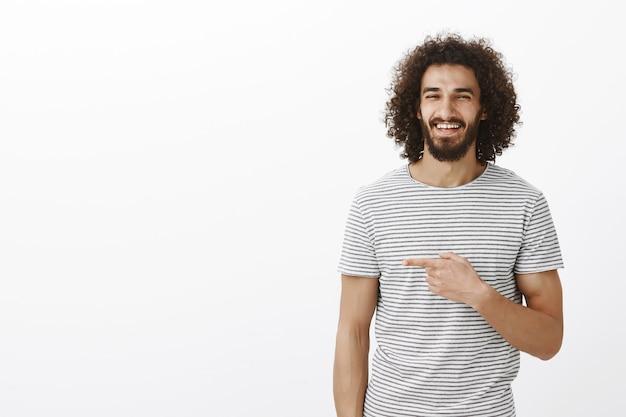 Homem bonito, feliz e despreocupado com barba em uma elegante camiseta listrada, rindo de alegria e apontando para a esquerda com o dedo indicador