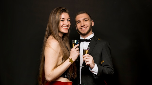 Homem bonito feliz e mulher atraente com copos de bebidas e confetes