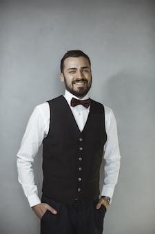 Homem bonito feliz e sorridente de colete preto e gravata borboleta, olhando para a câmera.