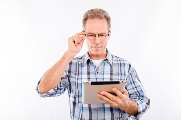 Homem bonito feliz envelhecido de óculos segurando um tablet