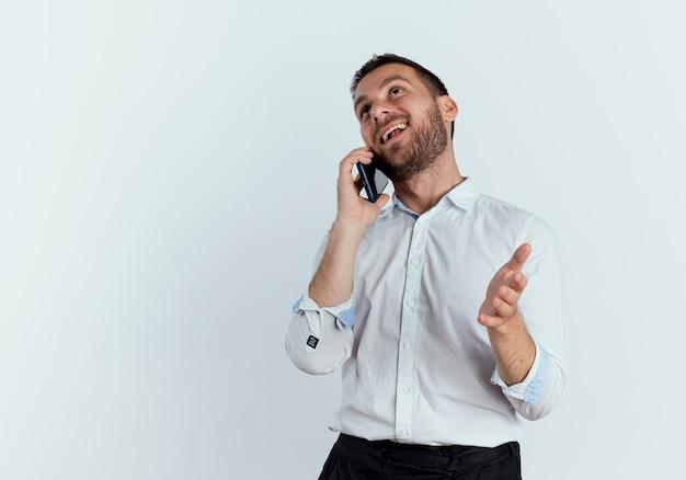Homem bonito feliz falando no telefone olhando isolado na parede branca