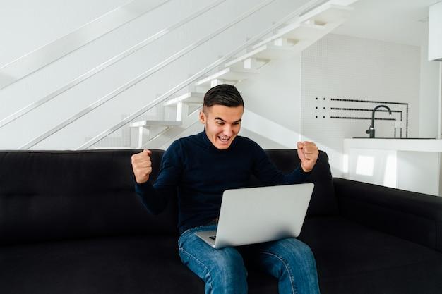 Homem bonito feliz levantou as mãos, depois de ganhar na loteria, sucesso impressionante.