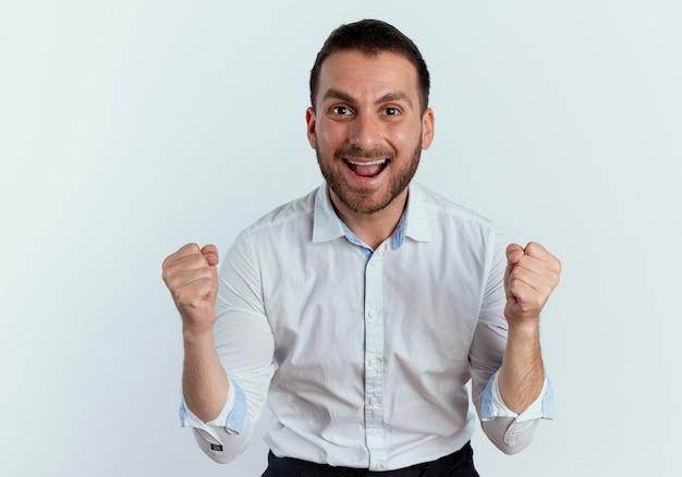 Homem bonito feliz mantendo os punhos parecendo isolados na parede branca