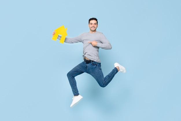 Homem bonito feliz pulando e apontando para o modelo de casa amarelo isolado
